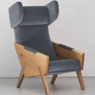 szary nowoczesny fotel uszak z dębowymi bokami